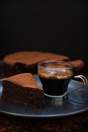 flourless chocolate cake: A slice of flourless olive oil chocolate cake with a cup of hot coffee on a black plate. Dark food photography. Stock Photo