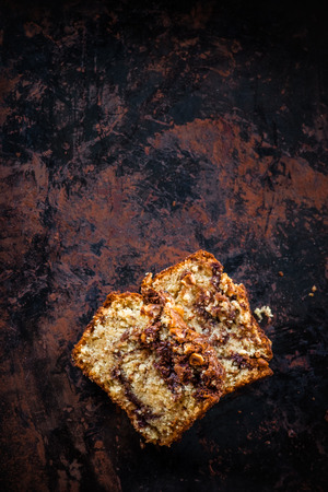 banana bread: Top view of two pieces of banana bread with swirl and chopped hazelnuts on dark background. Dark food photography. Free text space. Stock Photo