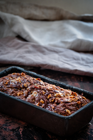 banana bread: Banana bread with swirl and chopped hazelnuts in the baking pan. Dark food photography. Free text space. Stock Photo