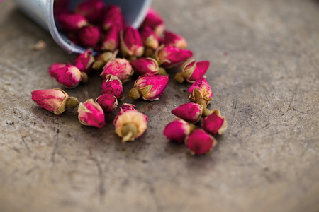 detoxing: Small dried  pink rose buds on a dark background