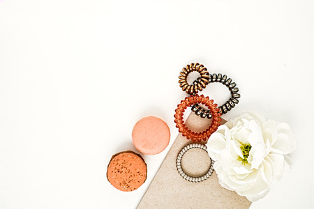bloggers: Feminine hair accessories - spiral rubber bands and flower and macarons. Flat lay for fashion bloggers. White background. Copy space for text.