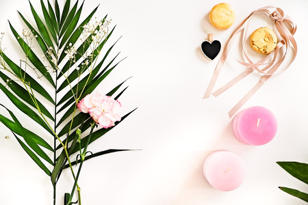 Beauty blogger flat lay on white.  Green leaves and carnation flower, pink ombre candles, heart, macaroons. Woman decorating ideas. Negative space for text