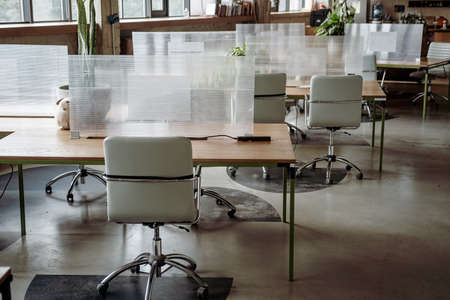 Co-working space with separated plastic boards between tables. Nnew normal, maintain social distancing. Freelance working place