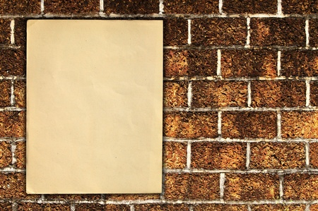 describe: Old paper on brick wall