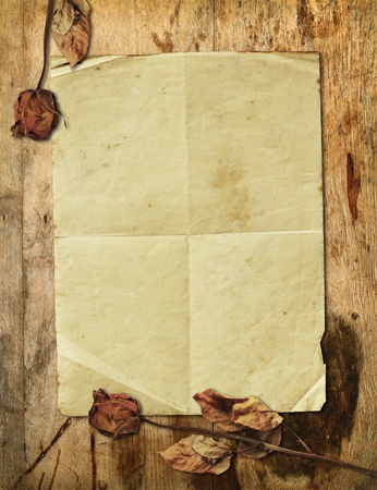 Old paper with dried rose on wooden background photo