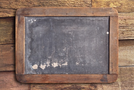 Grunge slate board on wooden background   photo