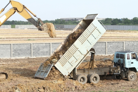 Backhoe and dump truck on construction site photo