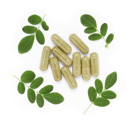 Moringa oleifera capsule with green fresh leaves on white background