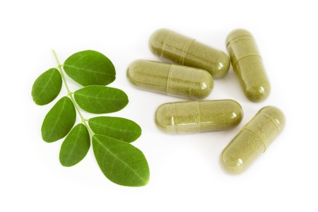moringa: Moringa oleifera capsule with green fresh leaves on white background