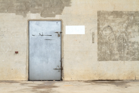 Grunge concrete wall with old metal door photo