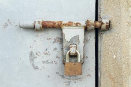 Rusty door latch with padlock photo