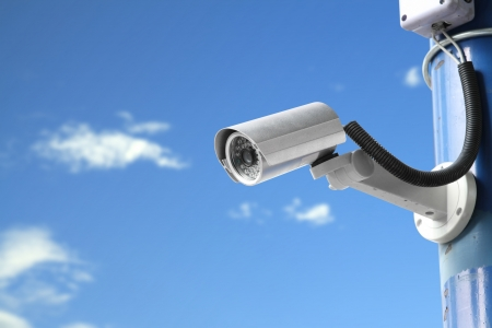 security cameras: Security camera on blue sky background