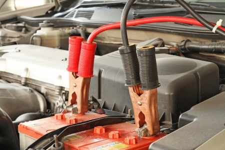 Jumper cables charging battery on a car 스톡 콘텐츠