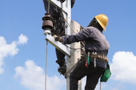 electricidad industrial: Electricista arreglando poste de energía eléctrica