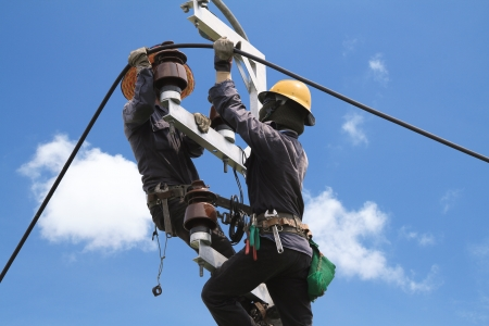 electrical engineer: Electricista arreglando poste de energía eléctrica