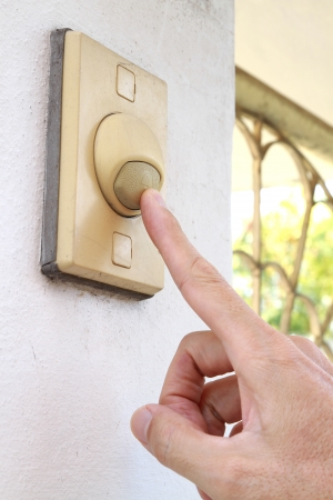 door bell: Finger pressing bell switch button Stock Photo