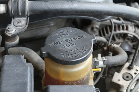 Power steering fluid cap with warning label in a car Stock Photo