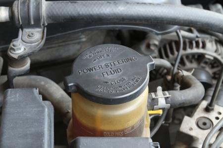 Tappo Olio del servosterzo con etichetta di avvertimento in una macchina