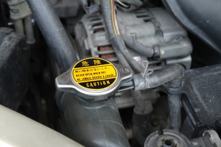 Radiator cap with warning label in a car Stock Photo