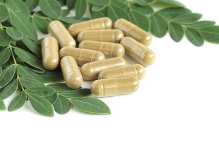 oleifera: Moringa ole�fera c�psula con hojas verdes frescas en el fondo blanco
