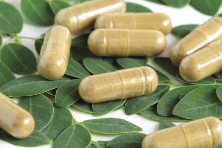 oleifera: Moringa oleifera capsule with green fresh leaves on white background