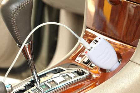 USB adapter converter plug with charging cable on a car photo