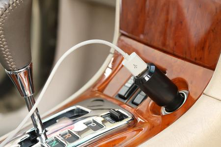 encendedores: Clavija del cargador USB con cable de carga en un coche Foto de archivo