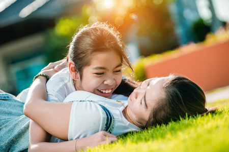 Mother and daughter lying and happily hugging the Park lawn in front of their home on mothers day Festival.