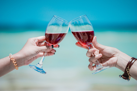 Young Asian woman wearing Hawaiian with hat and sunglasses is happy when they go to the beach for a holiday. Drinking a glass of wine together. Stock Photo