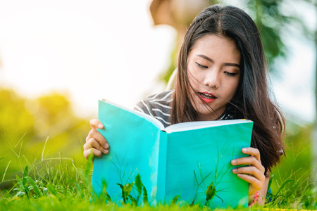 Asian teenage girl reading a book in the park on Sunday morning, a brilliant weekend. The women students are reading books, intended to prepare for university entrance exams. Reklamní fotografie