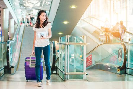 Les femmes asiatiques transportaient des bagages autour de l'aéroport international. Elle voyageait à l'étranger pour voyager le week-end. Banque d'images - 85366200