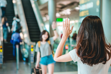 Asian teen women greet her friends when her arrival at the airport. Stockfoto