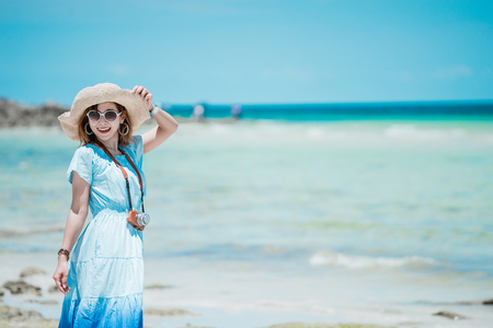 when: Young Asian woman wearing Hawaiian with hat and sunglasses is happy when they go to the beach for a holiday. Stock Photo