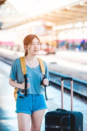 手荷物鉄道プラットフォーム領域を待っているアジアの十代の少女は、週末にタイ国の地方観光に行く準備ができて準備。バンコクからチェンマイ 写真素材