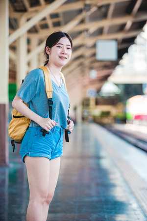 Teen Asian girl waiting for checked baggage train platform area prepared to ready to go sightseeing by the provinces in the country, Thailand on weekends. From Bangkok to Chiang Mai