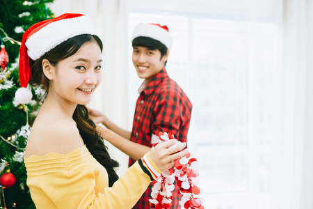 Young Asian teens are decorating the Christmas tree and party at their home. BCE to celebrate the coming 2018.