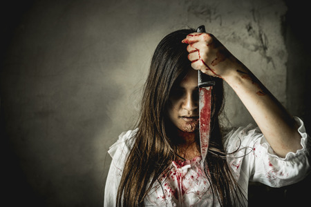 Asian girl dress killer to Halloween festival She's holding a kitchen knife and a big soaked with blood with terrible eyes ready to kill people. Foto de archivo