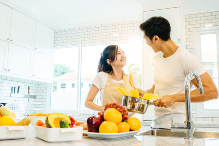 Asian teen couple are helping to make dinner. And bakery together happily. On Valentines Day in their home.