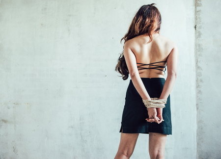 Office girl who unfortunately was kidnapped at the abandoned house and raping her. And tightly bound with rope. She was stripped shirt off, leaving only underwear. Stock Photo