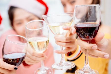 Groups of friends are Asian men and women decorated the Christmas tree. To celebrate the Christmas season. They drink wine and champagne to enjoy together happily.