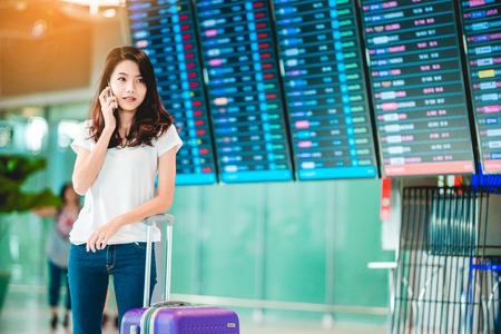 Asian teenage girl is using a smartphone to check flight at the international airport to travel on weekends. Stock Photo
