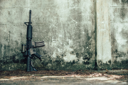 M4A1 (AR-15), M-16 assault rifle gun for the American military is placed beside the old wall. Stock Photo