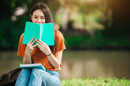 A young or teen asian girl student in university smiling and reading the book and look at the tablet or labtop computer in summer holiday. Standard-Bild
