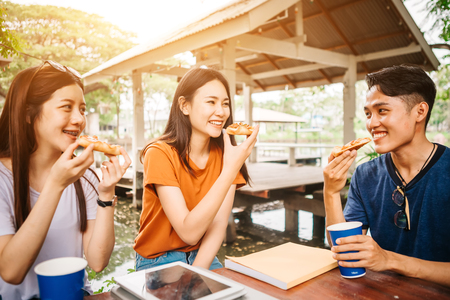 Asian students eating eating the pizza together in breaking time early next study class having fun and enjoy party, Italian food slice with cheese delicious at university outdoor.