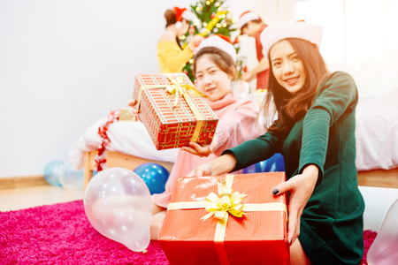 Groups of friends are Asian men and women decorated the Christmas tree. To celebrate the Christmas season. They drink wine and champagne to enjoy together happily. Close focus to gifboxes.