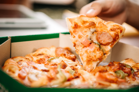 Man picking up a lice of hot pizza large cheese lunch or dinner crust seafood meat topping sauce with bell pepper or vegetables by delicious tasty, italian traditional fast food in peper board box on table in side view. Stock Photo