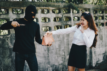 Thieves were threatened with a knife office girl on the way she was walking home. Stock Photo