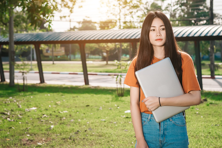 A young or teen asian girl student in university and holding the laptop computer in summer holiday in the park. Stock Photo