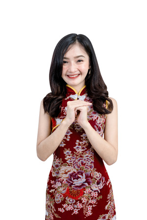 An Asian girl in Cheongsam or Qipao dress is smiling and happy emotion to you in Chinese New Year festival concept. Image contained clipping path.