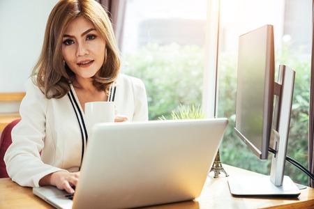 Bedrijfs vrouw die een kop van koffie drinkt en haar laptop voor het werken in wat heldere ochtend met behulp van. Stockfoto - 96164790